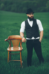 man with a beard  thinking in the field near chair