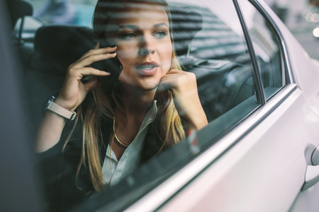 Businesswoman making phone call in taxi