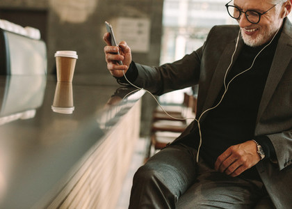 Smiling businessman in cafe listening to music with phone