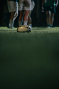 Rugby ball on grass with teams in background