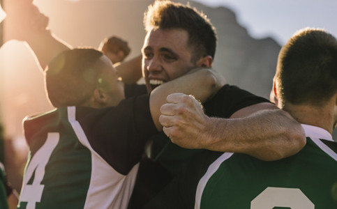 Team of rugby players cheering after victory