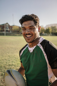 Smiling rugby player smeared in mud