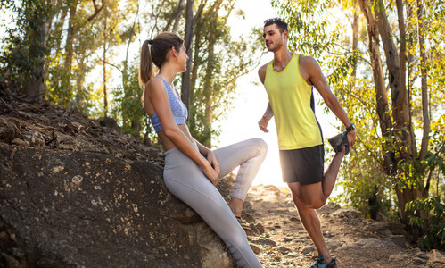 Couple taking break after mountain trail running workout