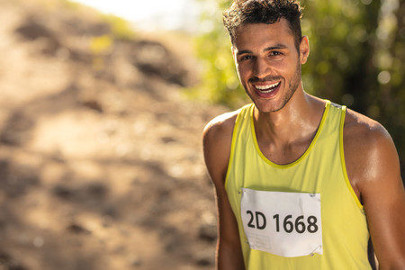 Smiling male athlete in mountain trail race