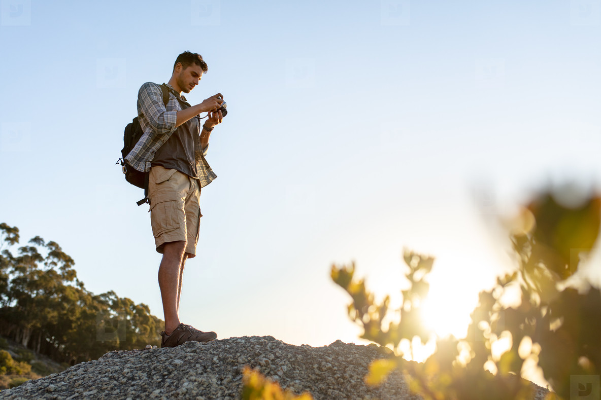 Male hiker with camera on hill top