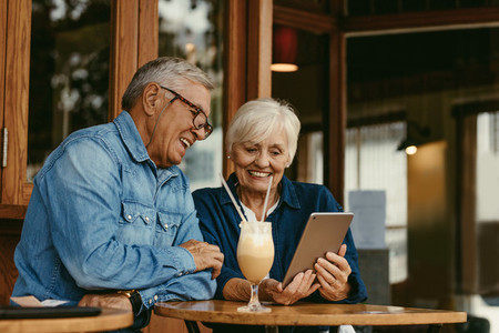 Senior couple at cafe using digital tablet