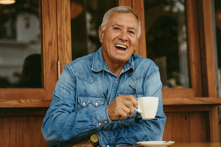 Cheerful senior man having coffee at cafe
