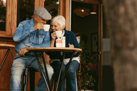 Senior couple relaxing at cafe and having coffee