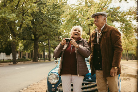 Senior couple taking picture on car trip