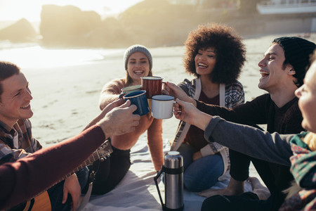 Multi ethnic friends toasting coffee mugs at the beach