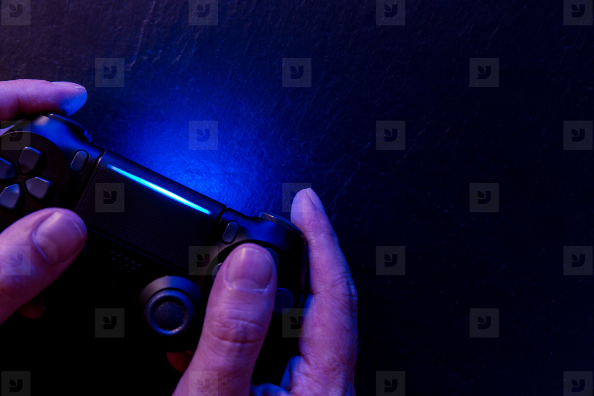 Man playing video game with controller at night lights