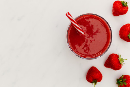 Red smoothie strawberries drink white background