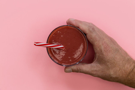 Hand holding red strawberry smoothie drink pink background