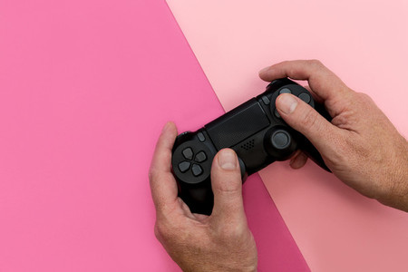 Man playing video game with controller bright pink background