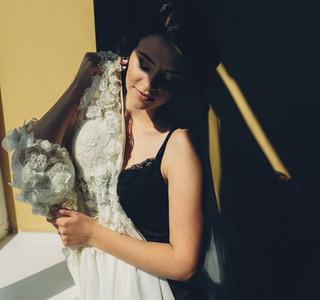 bride sitting holds wedding dress