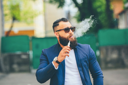 well dressed man smoking electronic cigarette