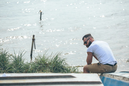 American Bearded Man looks on the river bank