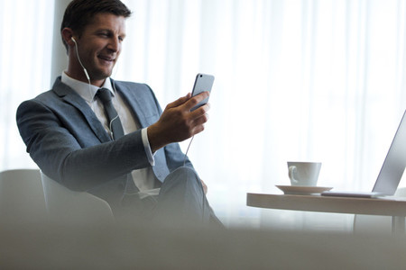 Businessman with smartphone having video call