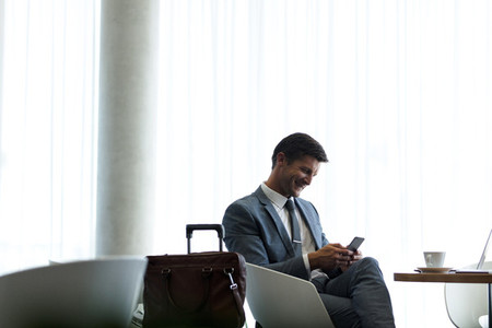 Businessman at airport lounge using mobile phone