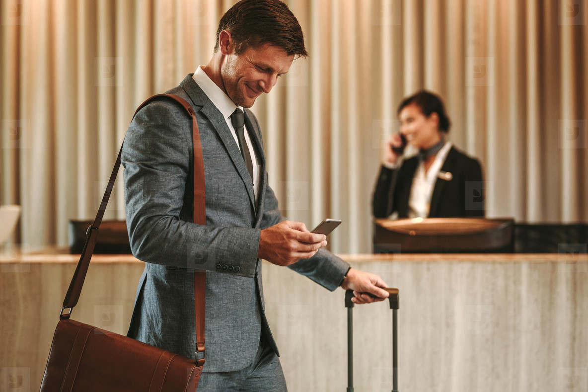 Businessman in hotel hallway with cellphone and luggage