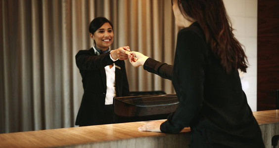 Female guest taking room key card at check in desk