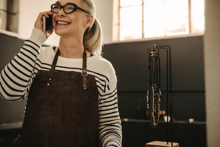 Female goldsmith taking on phone at design studio