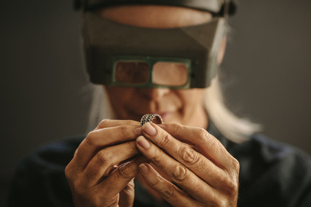 Professional jeweler inspecting a ring