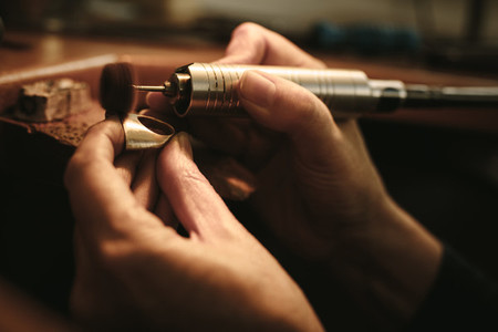 Jeweler making gold ring