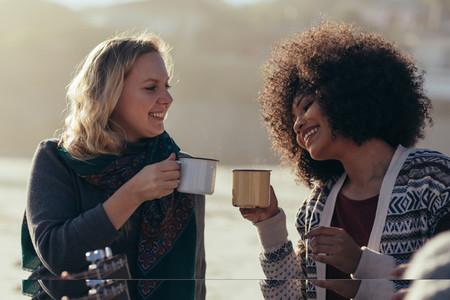Female friends having coffee at the beach
