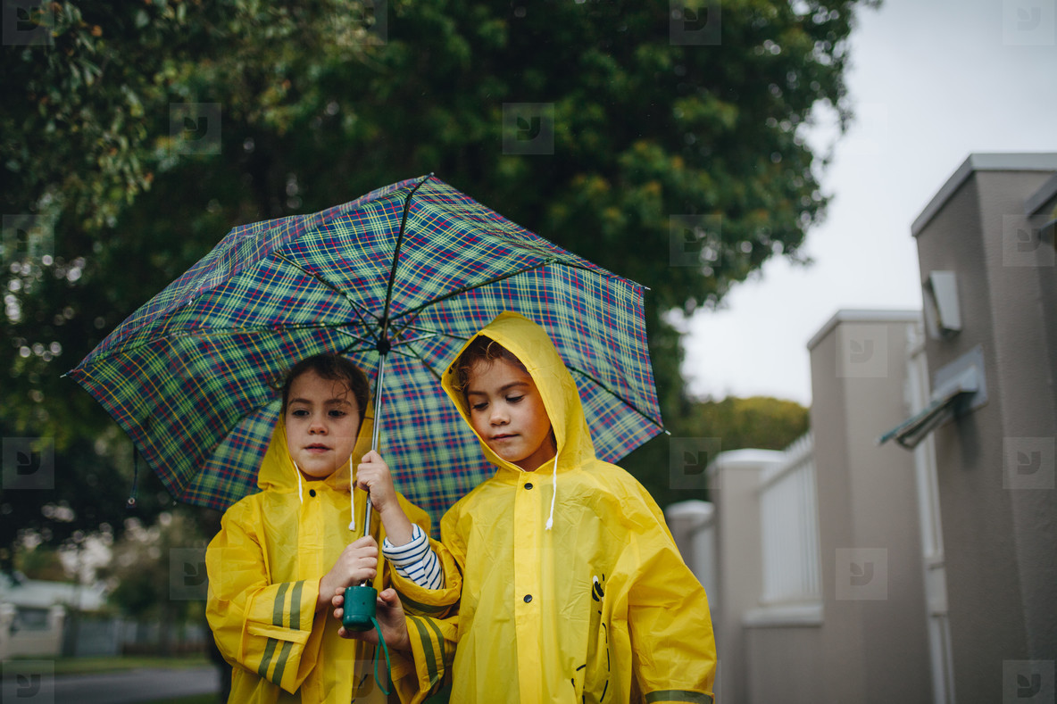 Two little girls with umbrella outdoors on rainy day