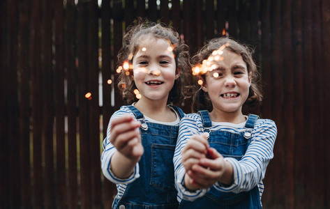 Little girls holding sparklers outdoors