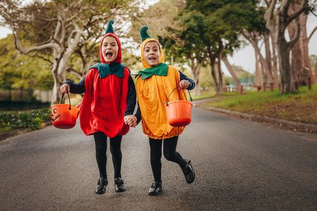 Cute little girls trick or treating in halloween costume