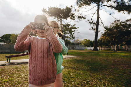 Twin sisters taking pictures with old camera at the playground