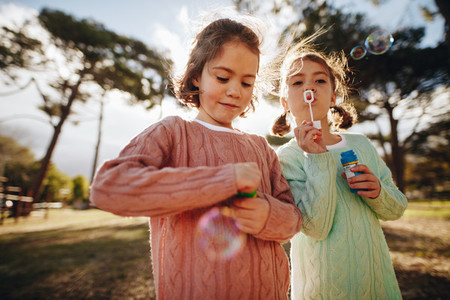 Sisters playing with soap bubbles at park