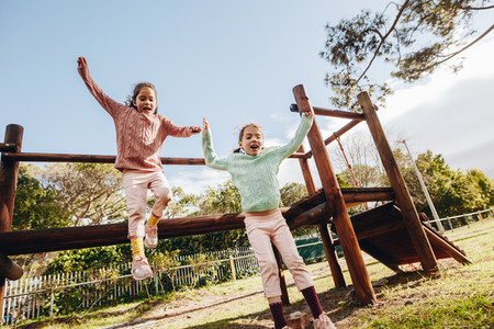 Happy little girls playing at outdoor playground