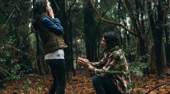 Man proposing his girlfriend at forest