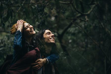 Loving couple piggybacking in the rain