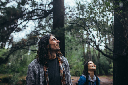 Man admiring the nature with woman at back in forest