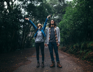 Couple having fun in rain in forest