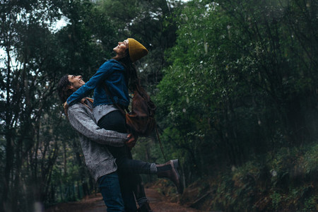 Yung couple enjoying in rain at forest