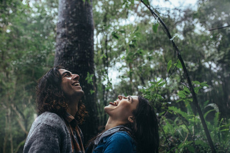 Couple catching raindrops on tongue in rainforest