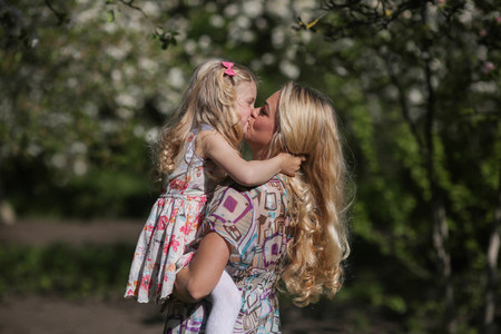 daughter kisses mom in the garnde