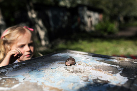 girl with a snail in the garden