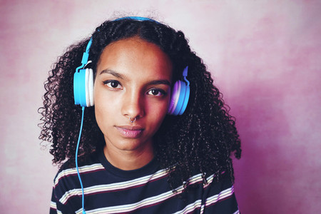 Studio portrait of a young woman listening to music