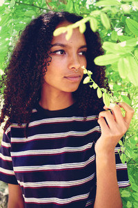 Beautiful young woman surrounded by green leaves