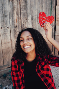 Cheerful young woman with a heart