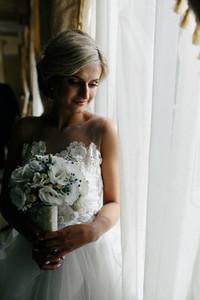 beautiful bride in a wedding dress  by window