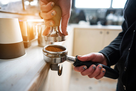 Barista presses ground coffee using tamper