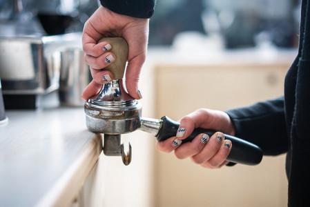 Barista presses ground coffee using tamper