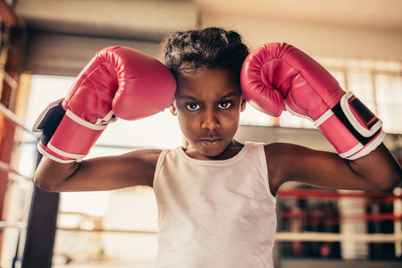 Boxing kid wearing gloves standing in a boxing gym